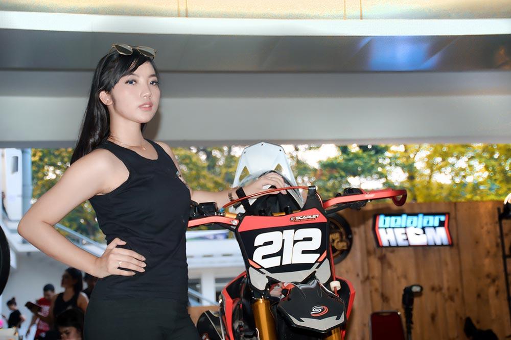 SPG menunjukkan motor di salah satu booth pada pemeran IIMS Motobike Expo 2019 di Istora Senayan, Jakarta, Minggu (1/12/2019)